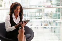 Mixed race businesswoman using digital tablet, to camera Stock Image