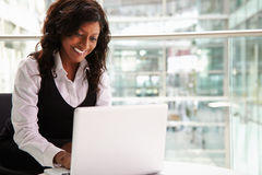 Mixed race businesswoman using laptop computer Royalty Free Stock Photo