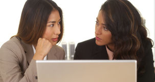 Mixed race businesswomen working on laptop Stock Image
