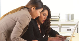 Mixed race businesswomen working together on computer stock photos