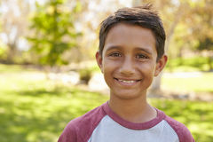Mixed race Caucasian Asian boy in park looking to camera Stock Images