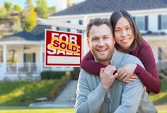 Mixed Race Caucasian and Chinese Couple In Front of Sold For Sale Sign. Mixed Race Caucasian and Chinese Couple In Front of Sold For Sale Real Estate Sign and Stock Photo