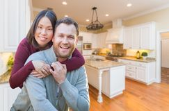 Mixed Race Caucasian and Chinese Couple Inside Beautiful Custom Kitchen Royalty Free Stock Photos