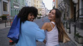 Mixed race and caucasian girls with bags smiling stock video