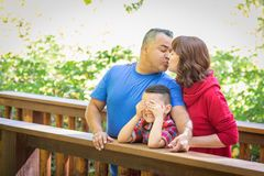 Mixed Race Caucasian and Hispanic Couple Kissing At The Park. Mixed Race Caucasian and Hispanic Family At The Park royalty free stock images
