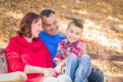 Mixed Race Caucasian and Hispanic Family Relaxing. Mixed Race Caucasian and Hispanic Family At The Park royalty free stock images