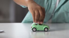 Mixed-race child rolling toy car over table surface, playtime, future dreams. Stock footage stock footage