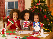 Mixed race children making Christmas cards stock images