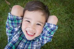 Laughing Mixed Race Chinese and Caucasian Young Boy Relaxing On His Back. Mixed Race Chinese and Caucasian Young Boy Relaxing On His Back Outside On The Grass Royalty Free Stock Images