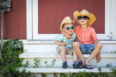 Mixed Race Chinese and Caucasian Young Brothers Having Fun Wearing Sunglasses and Cowboy Hats. On royalty free stock image