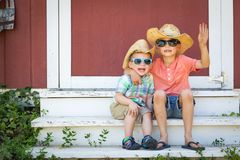 Mixed Race Chinese and Caucasian Young Brothers Having Fun Wearing Sunglasses and Cowboy Hats.  royalty free stock image