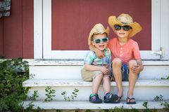 Mixed Race Chinese Caucasian Young Brothers Wearing Cowboy Hats. Mixed Race Chinese and Caucasian Young Brothers Having Fun Wearing Sunglasses and Cowboy Hats stock photo