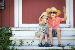 Mixed Race Chinese and Caucasian Young Brothers Having Fun Wearing Sunglasses and Cowboy Hats. Two Mixed Race Chinese and Caucasian Young Brothers Having Fun royalty free stock photography