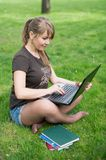 Mixed race college student sitting on the grass working Royalty Free Stock Images