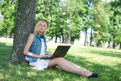 Mixed race college student sitting on the grass working Royalty Free Stock Photography