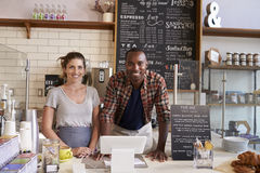 Mixed race couple behind counter at a coffee shop, close up Stock Images