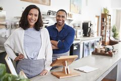 Mixed race couple behind the counter at their coffee shop royalty free stock image
