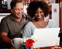 Mixed race couple in coffee house with laptop comp Stock Images