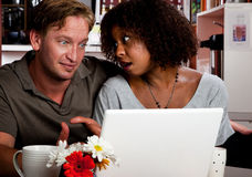 Mixed race couple in coffee house with laptop comp royalty free stock image