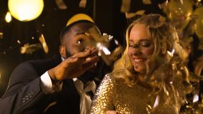 Mixed-race couple dancing at party under falling confetti, entertainment. Stock footage stock video footage