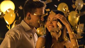 Mixed-race couple dancing under falling confetti at wedding party, celebration. Stock footage stock footage