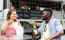 Mixed race couple eating and talking at food truck Royalty Free Stock Photo