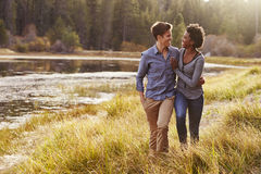 Mixed race couple embracing, walking near a rural lake Royalty Free Stock Photo