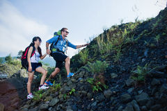 Mixed race couple go trekking together, walking on an uphill,   Stock Photos