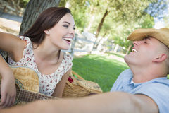 Mixed Race Couple with Guitar and Cowboy Hat in Park Stock Image