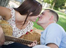 Mixed Race Couple with Guitar Kissing in the Park Stock Photography
