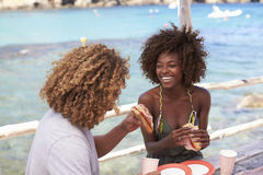 Mixed race couple having a meal by the sea, vertical, Ibiza Stock Image