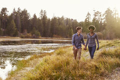 Mixed race couple holding hands, walking near a rural lake Royalty Free Stock Images