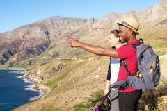 Mixed race couple on holiday by the seaside. Side portrait of happy young couple standing on a cliff enjoying the view Royalty Free Stock Photography