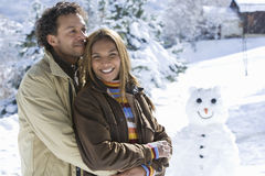 Mixed race couple hugging in snow, snowman in background Royalty Free Stock Image