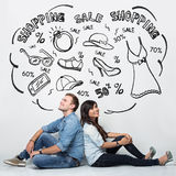 Mixed race couple imaginating about shopping, ilustrated things, stock photography