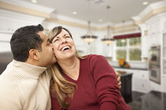 Mixed Race Couple Kissing Inside Beautiful Custom Kitchen Royalty Free Stock Photography