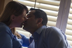 Mixed Race Couple Kissing Near the Light of the Wi Royalty Free Stock Photography