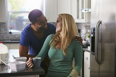 Mixed race couple in kitchen look closely at each other Royalty Free Stock Photography