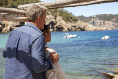 Mixed race couple looking out to sea from a jetty, back view Royalty Free Stock Photos