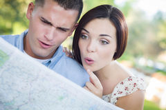 Mixed Race Couple Looking Over Map Outside Together Royalty Free Stock Images