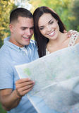 Mixed Race Couple Looking Over Map Outside Together Royalty Free Stock Image