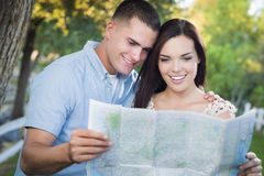 Mixed Race Couple Looking Over Map Outside Together Stock Images