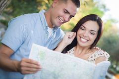 Mixed Race Couple Looking Over Map Outside Together Royalty Free Stock Photography