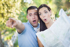Mixed Race Couple Looking Over Map Outside Together Royalty Free Stock Photos