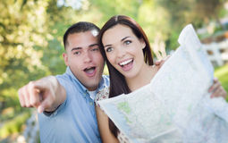 Mixed Race Couple Looking Over Map Outside Together Stock Photography