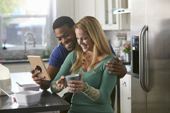 Mixed race couple looking at a tablet computer together in kitchen Royalty Free Stock Photography