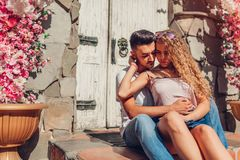 Mixed race couple in love hugging sitting by door outdoors. Arab man and white woman walking in city. stock photography