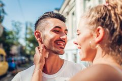 Mixed race couple in love walking in city. Arab man and his white girlfriend laughing. Young people hugging royalty free stock photos
