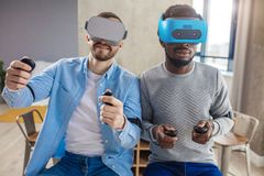 Mixed race couple of male friends develop project using virtual reality goggles royalty free stock image