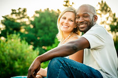 Mixed Race Couple at a Park. Beautiful mixed race couple or friends sitting at a park in the summer Royalty Free Stock Photos